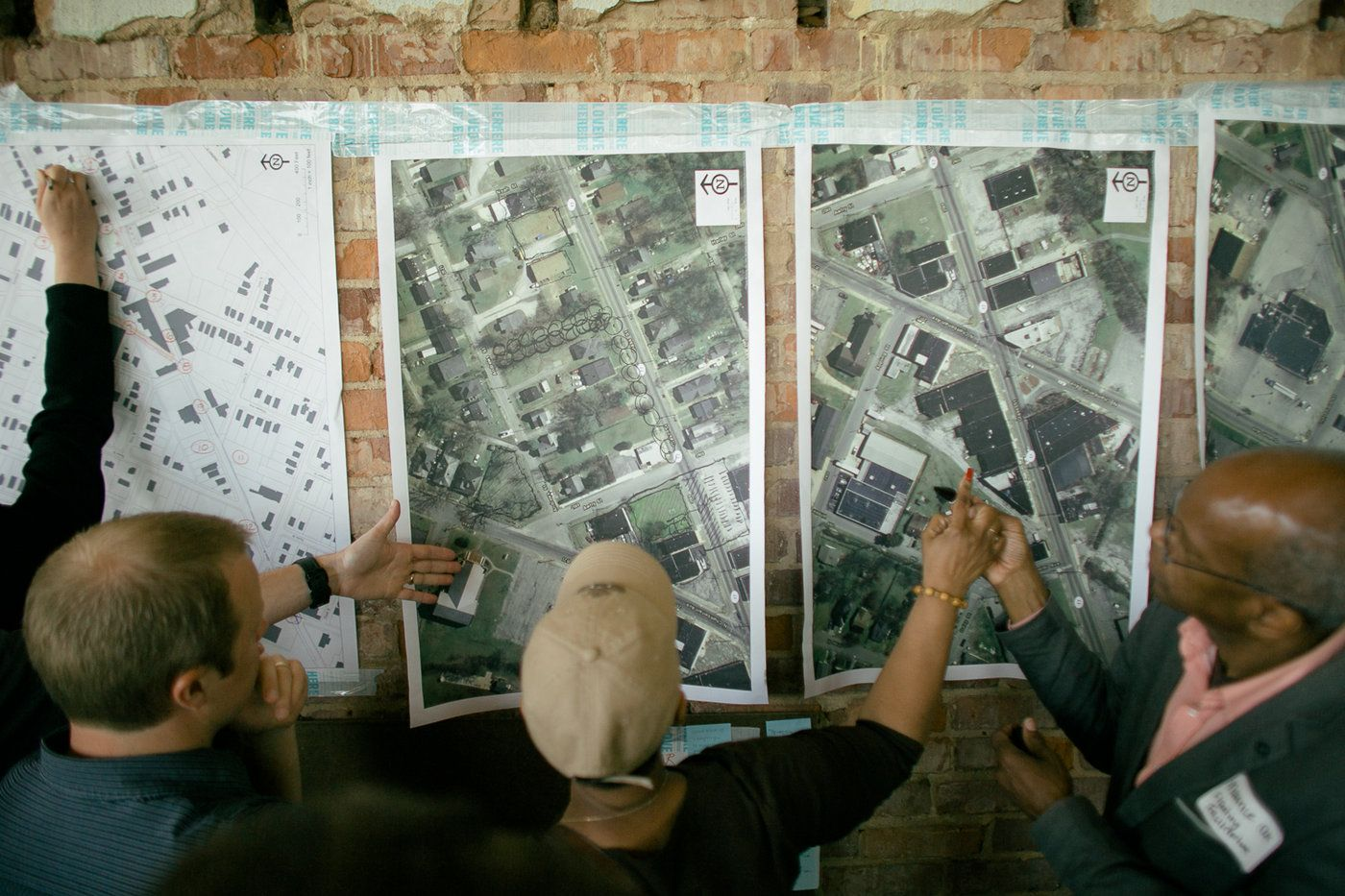 Medium shot of several people looking at printouts of a Chattanooga map.