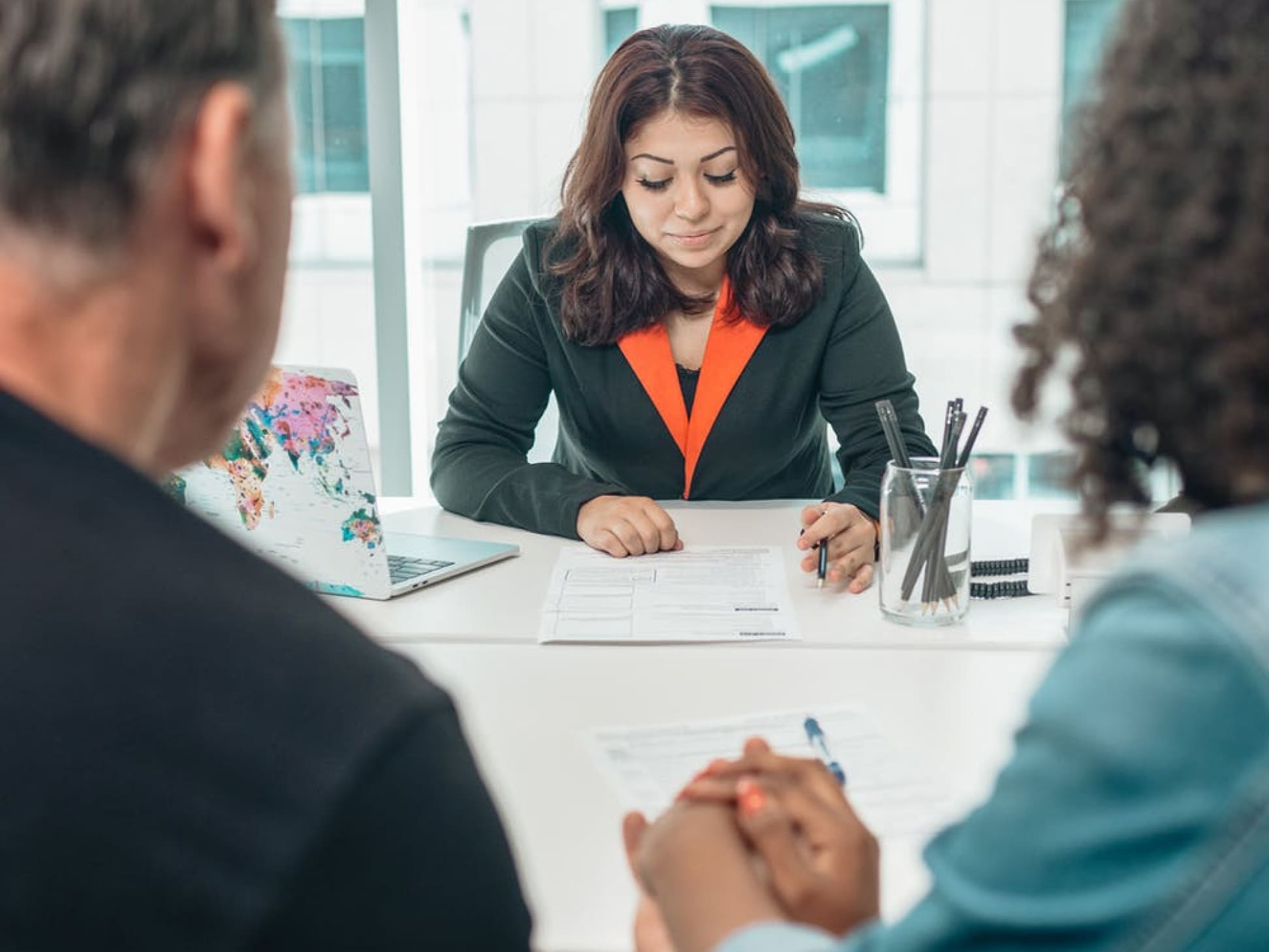 A couple meets with a financial advisor around a conference table.