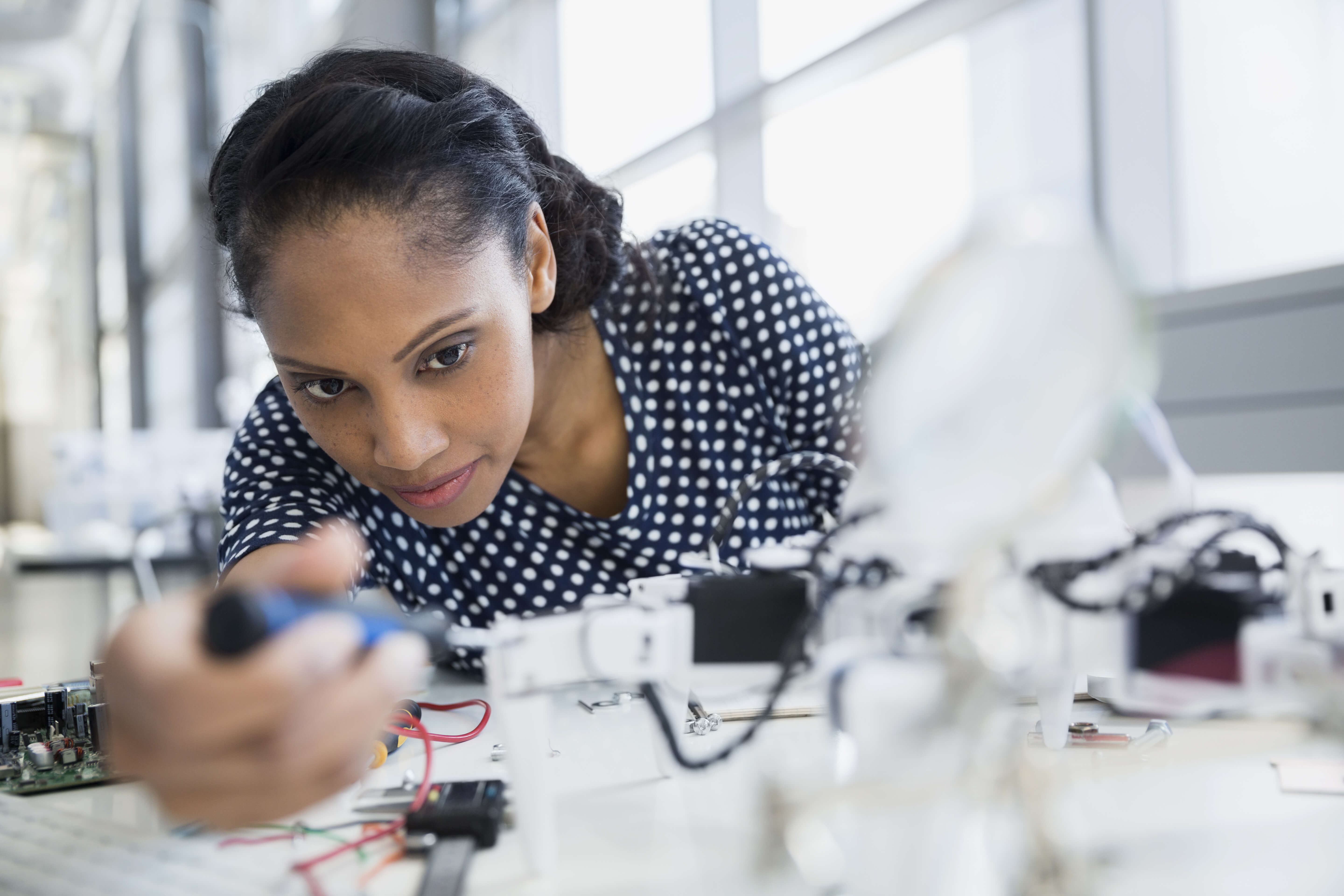 Image of a women working on a piece of machinery