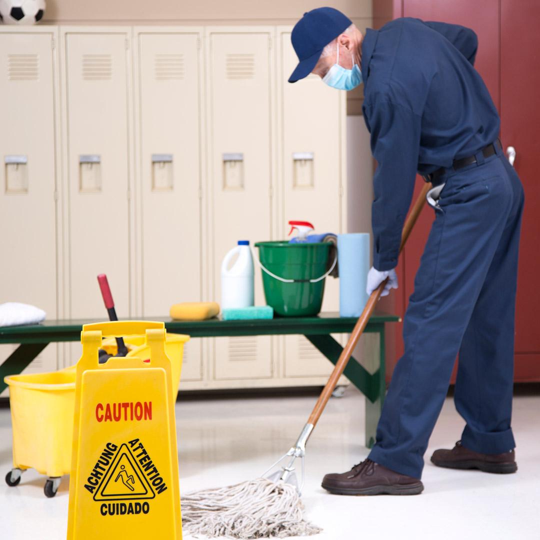 School custodian moping floor of locker room.