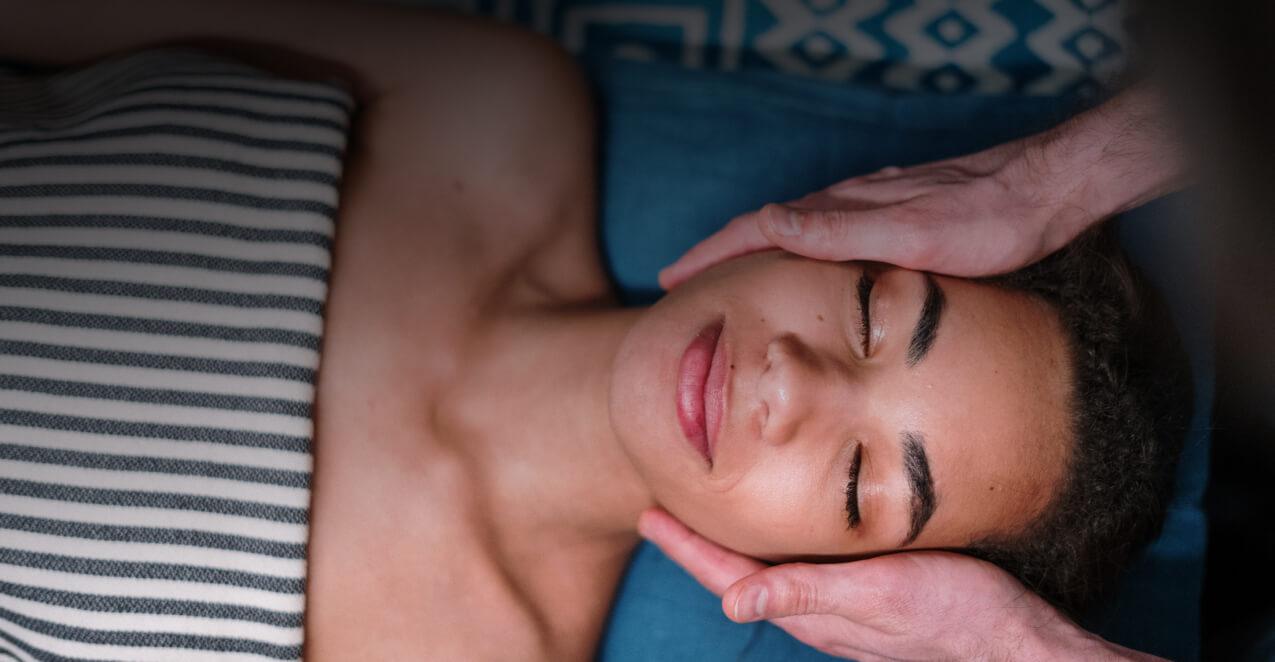 hands massaging a woman's head