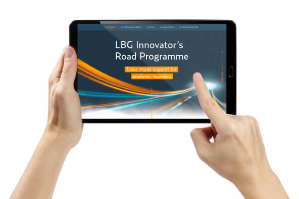 hands holding a tablet displaying the IECT-website