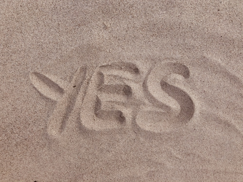 yes text on brown sand