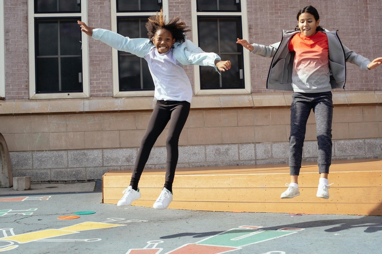 deux jeunes sautant en l'air dans la cours de recréatiob