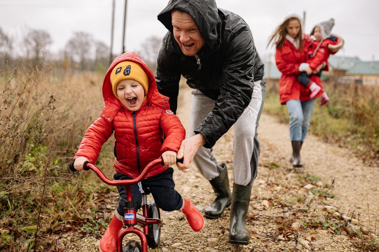 Famille sur une route de campagne avec un petit garçon à vélo