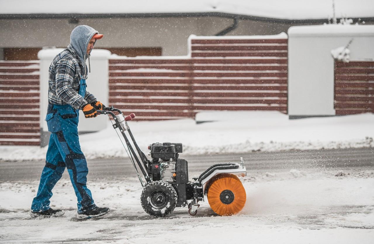 Man clearing sidewalk using snow removal power broom
