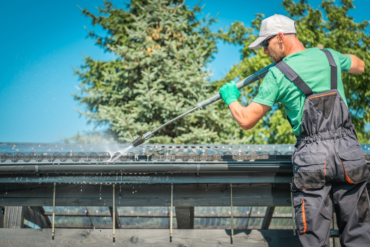 Man cleaning eavestrough with power washer equipment