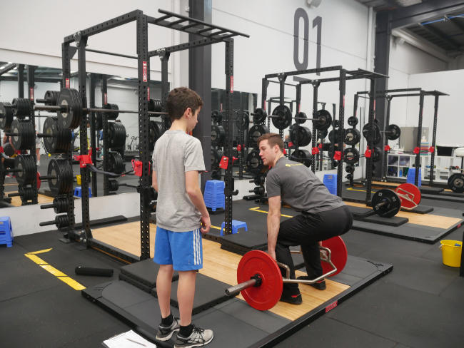 A young athlete learns to practice smart weight training