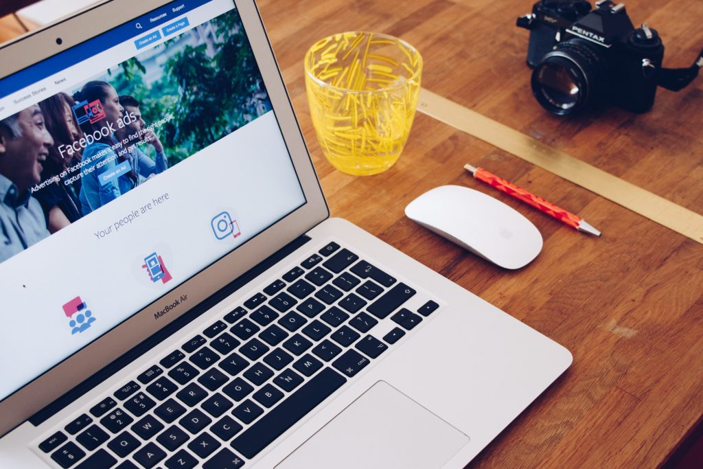 Laptop displaying Facebook Ads Manager platform. Next to the laptop is an Apple mouse, glass of water, pen and digital camera.