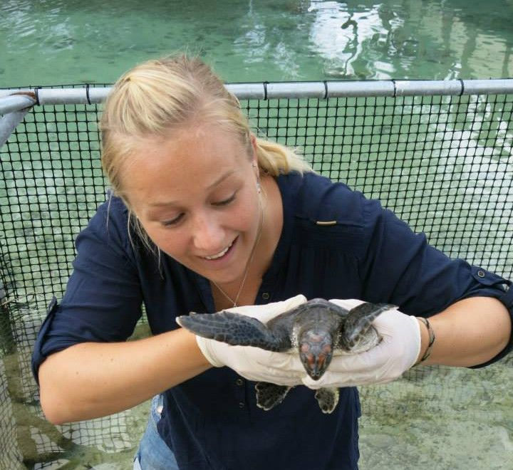 Tina smiling holding a turtle