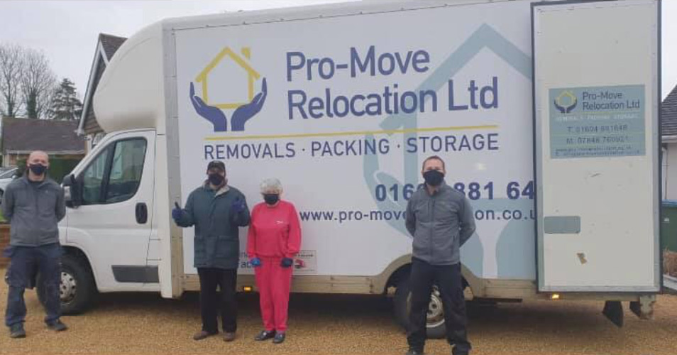 The Pro Move Team standing outside by a van with their COVID protection on