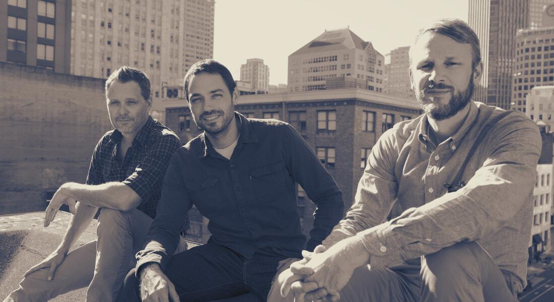 portrait of 3 men in a city