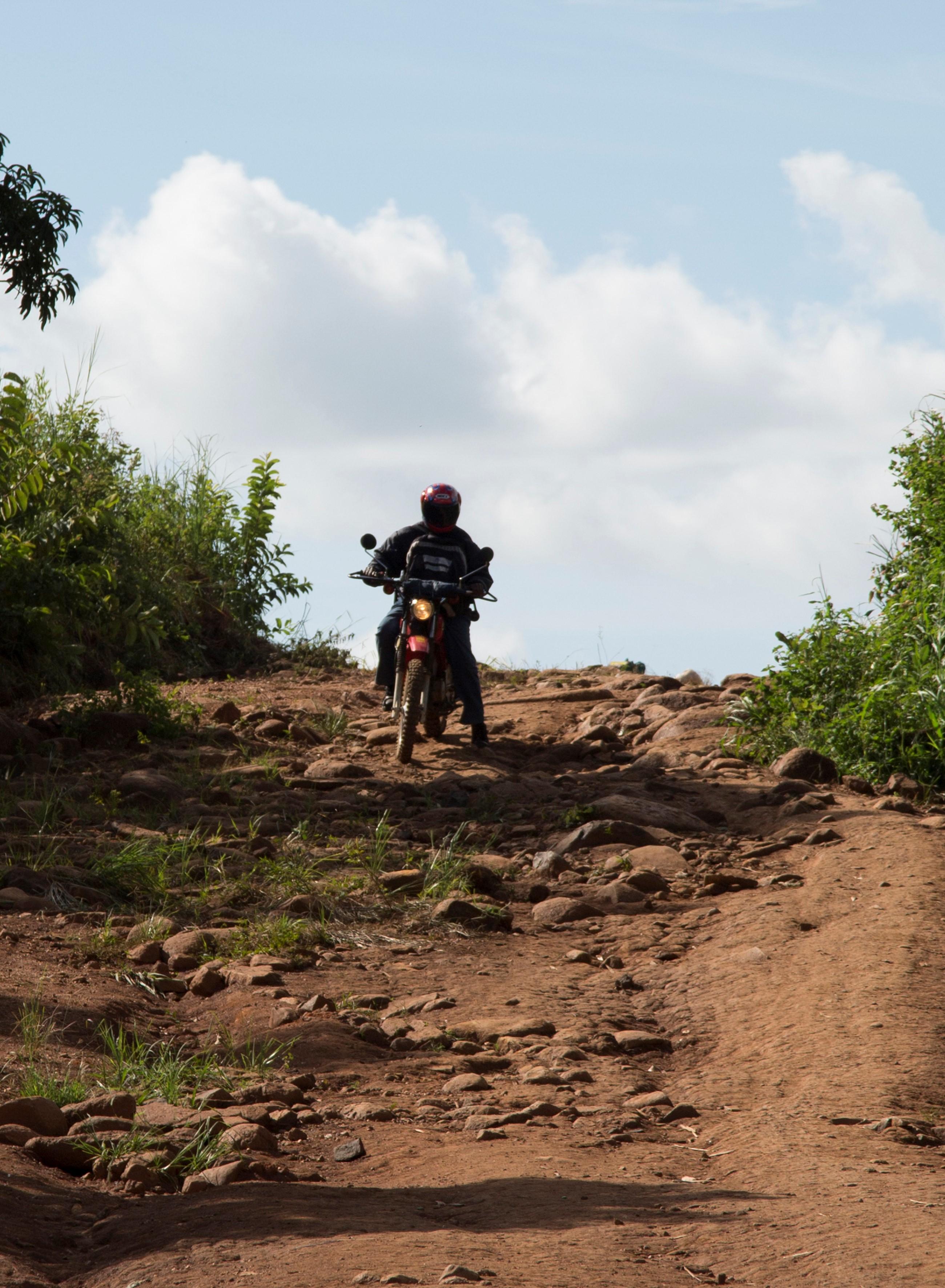 community health worker on motorbike on rural road