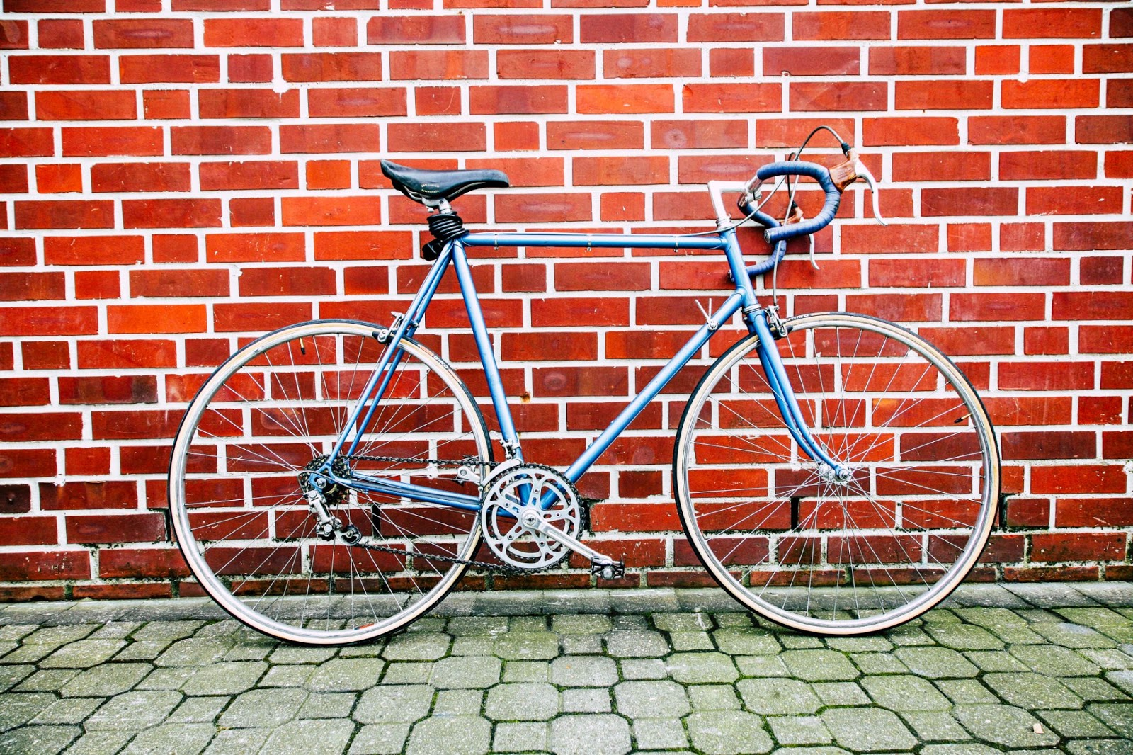blue bicycle parked in front of a red brick wall