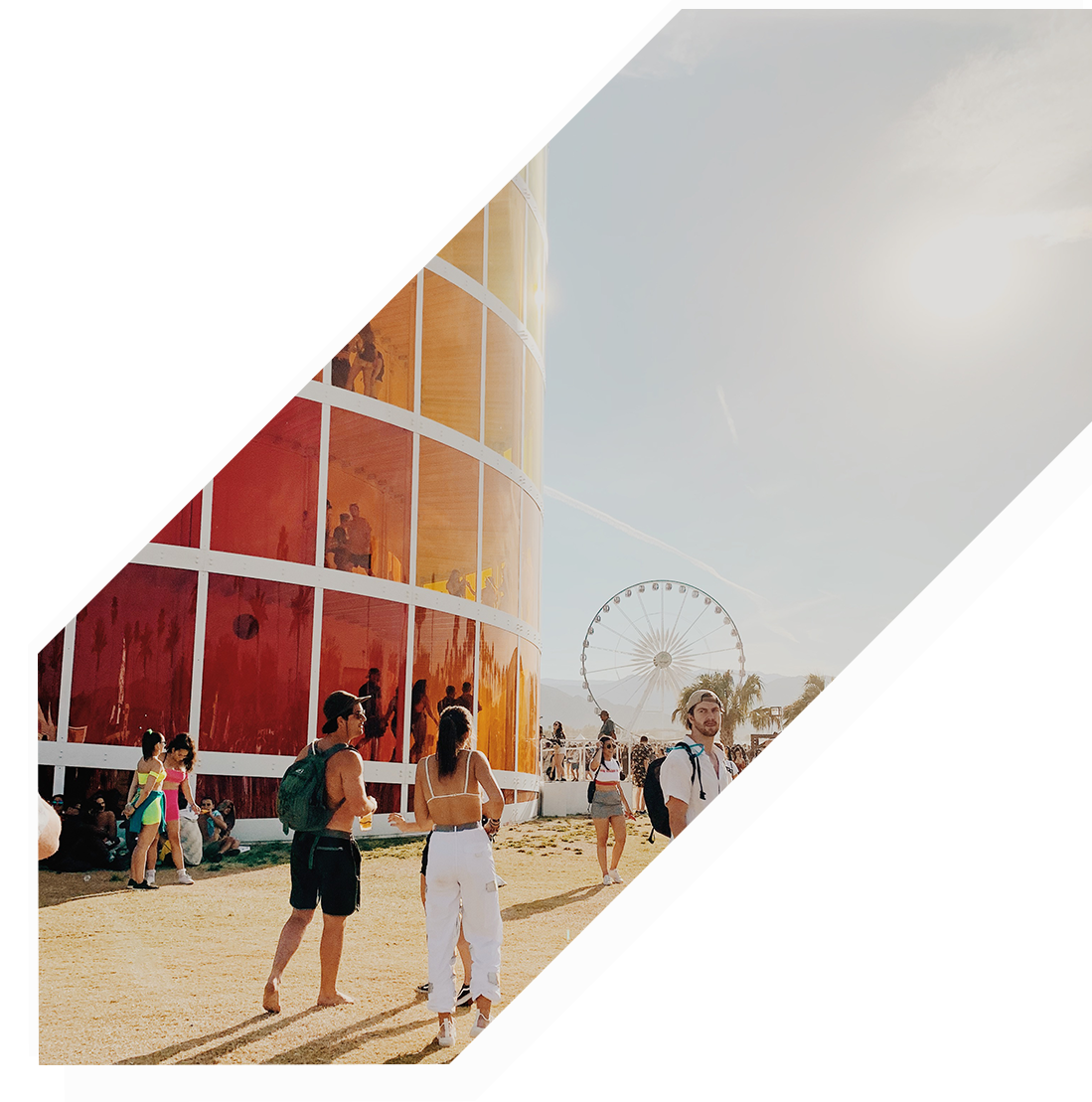 Two people walking on Coachella grounds next to a large orange tower.