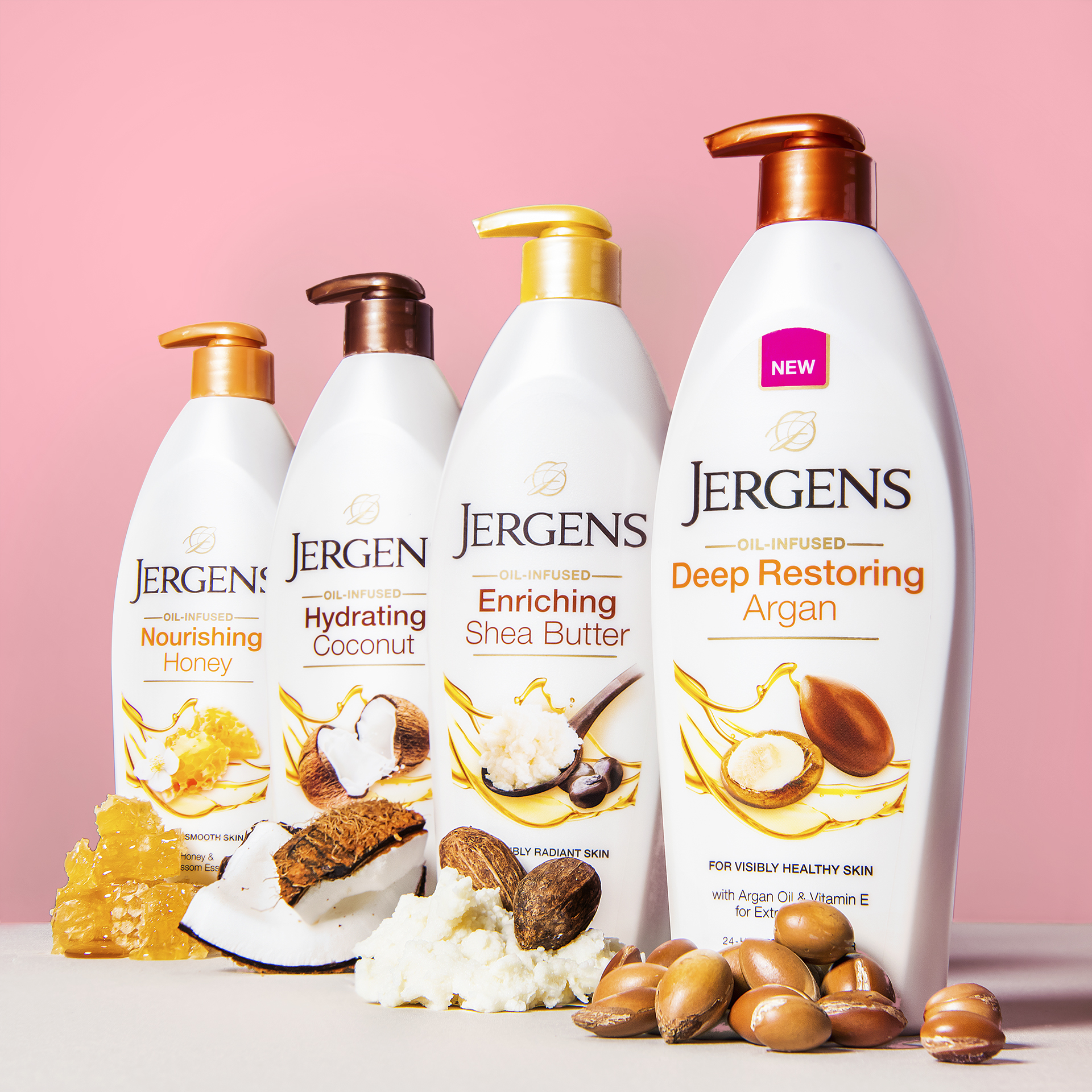 Line up of multiple Jergens Lotions products and ingredients such as argan nuts and honeycomb