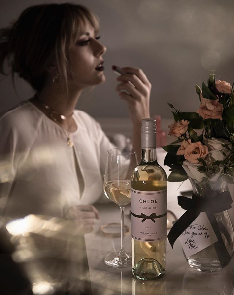 Woman applying lipstick with roses and Chloe Pinot Grigio in the forefront