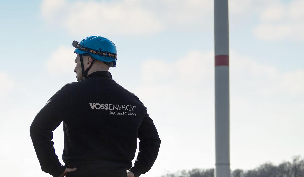 Mitarbeiter der Betriebsführung der Voss Energy GmbH vor Windkraftanlage.