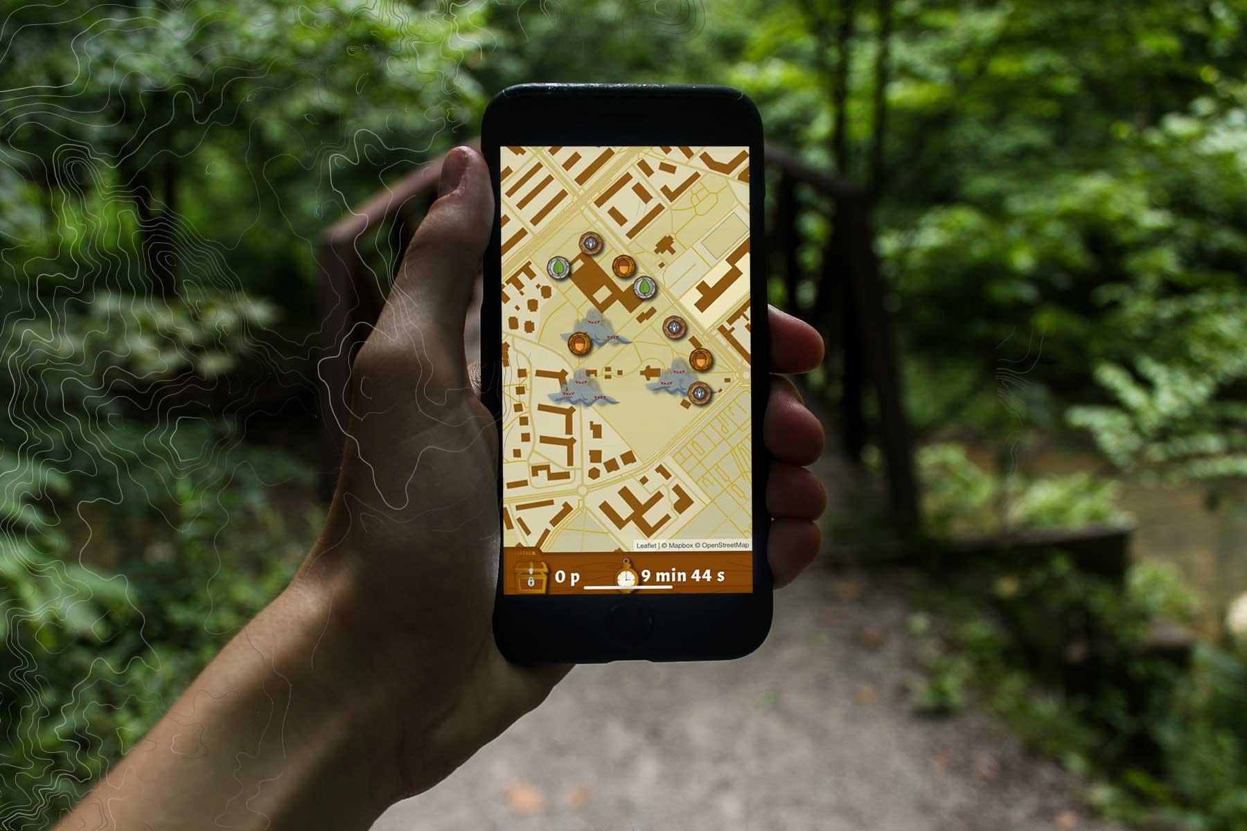 Hand med mobiltelefon och Run and Find i skogsmiljö