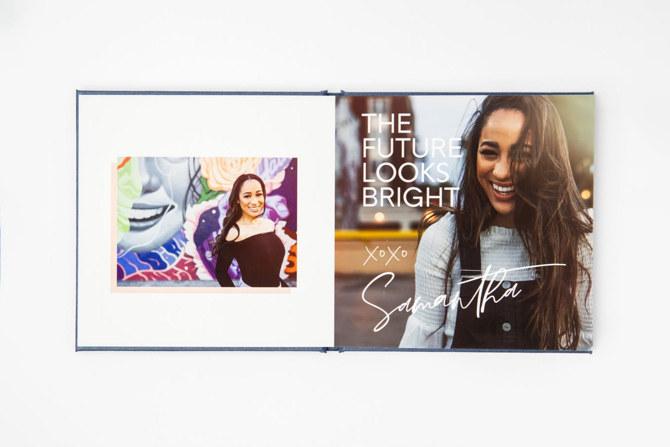 Open layflat book with two pictures of a senior graduate girl.