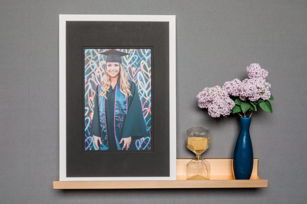 Framed Print of Senior Graduate Girl sitting on wall shelf.