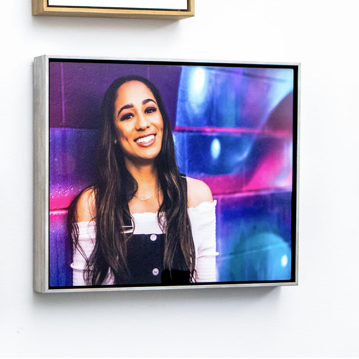Hanging float frame with an image of senior graduate girl.