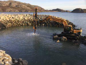 Gravemaskin med boretårn ved hav og molo