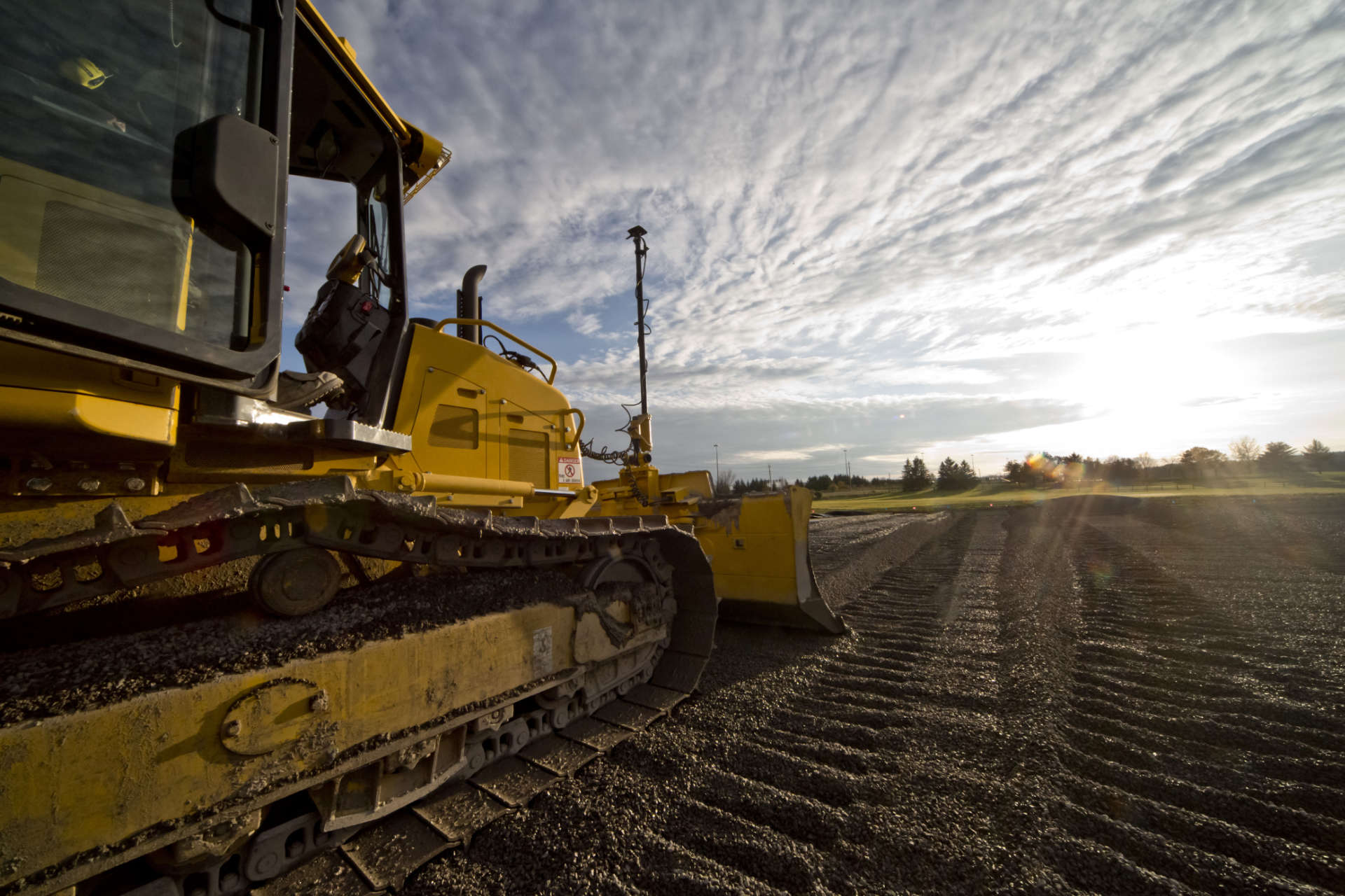 bulldozer in field with sky and clouds behind
