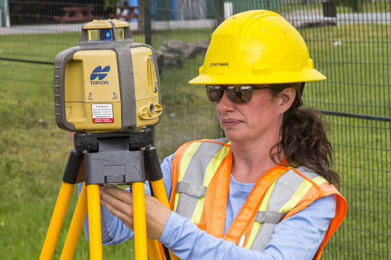 woman in safety vest and yellow hardhat looking at laser total station scanner