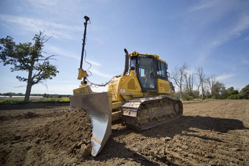 bulldozer moving dirt in a field near ottawa