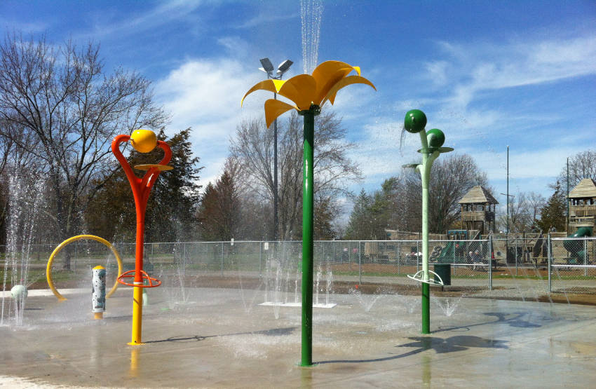 childrens splash pad play area with water shooting upward from concrete pad and decorative poles