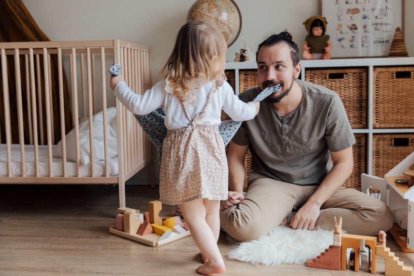 a father playing with his toddler daughter in a playroom with crib.