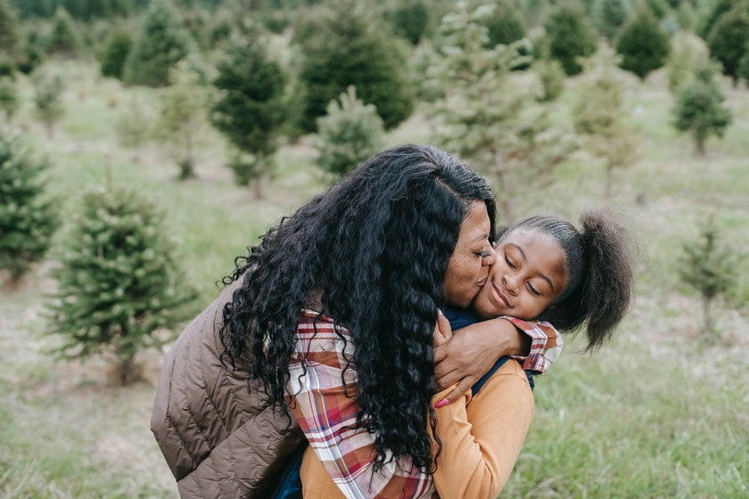 a mother hugging and kissing her teenage daughter in the grass