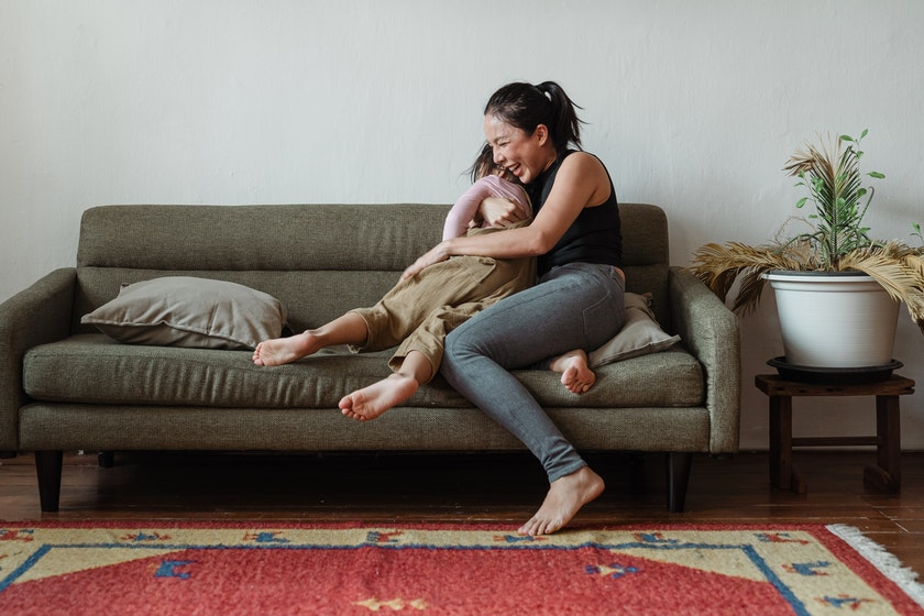 a mother on a green couch hugging and laughing with her toddler daughter
