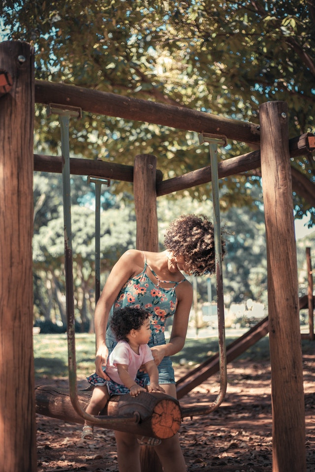 a mother pushing her toddler daughter on a swing in the park.