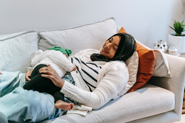 a mother laying on the couch with her sleeping daughter on her chest.