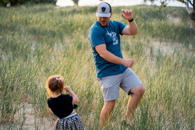 a father and toddler daughter dancing in a grassy field.