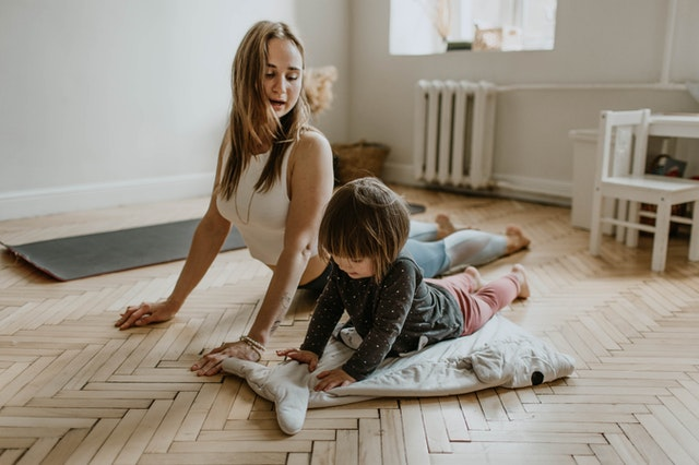 a mother and toddler daughter doing yoga on their living room floor.