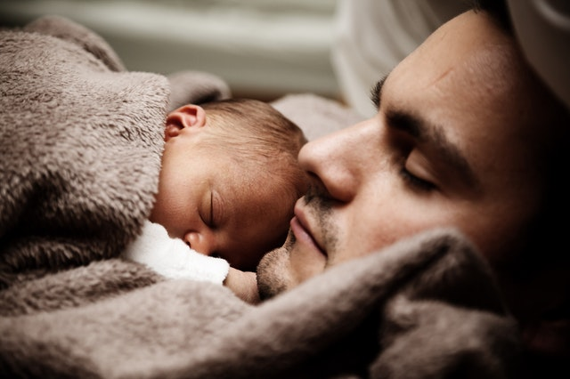 a newborn baby wrapped in blanket sleeping on father's chest.