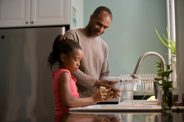 a father and middle school aged daughter cooking food in the kitchen.