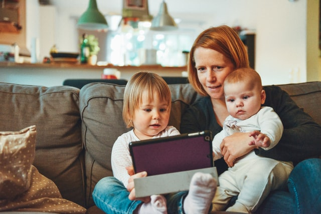 mother with baby and toddler on her lap showing them tablet screen.