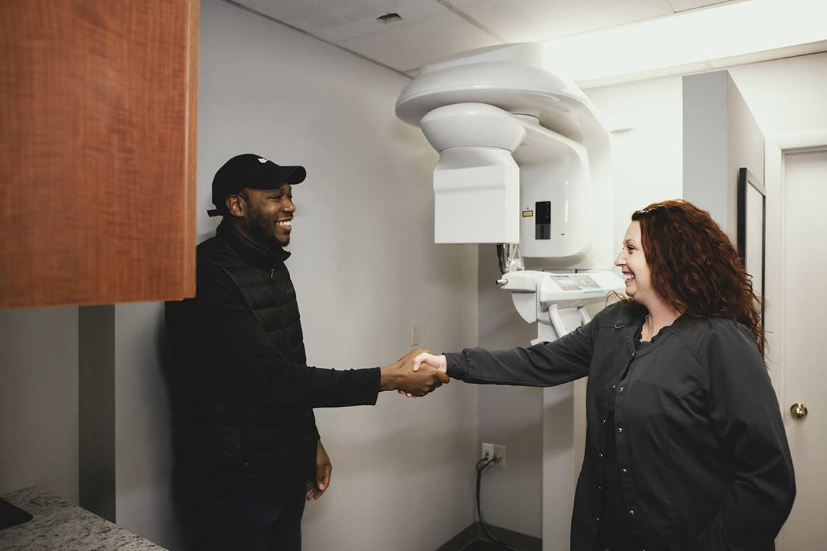 Photo of a patient and a team member shaking hands