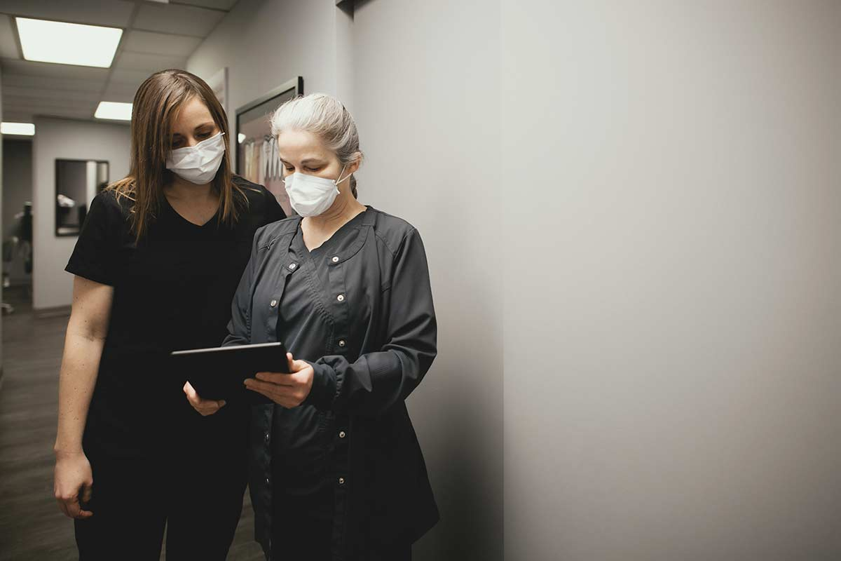 Photo of two team members reviewing information on a tablet