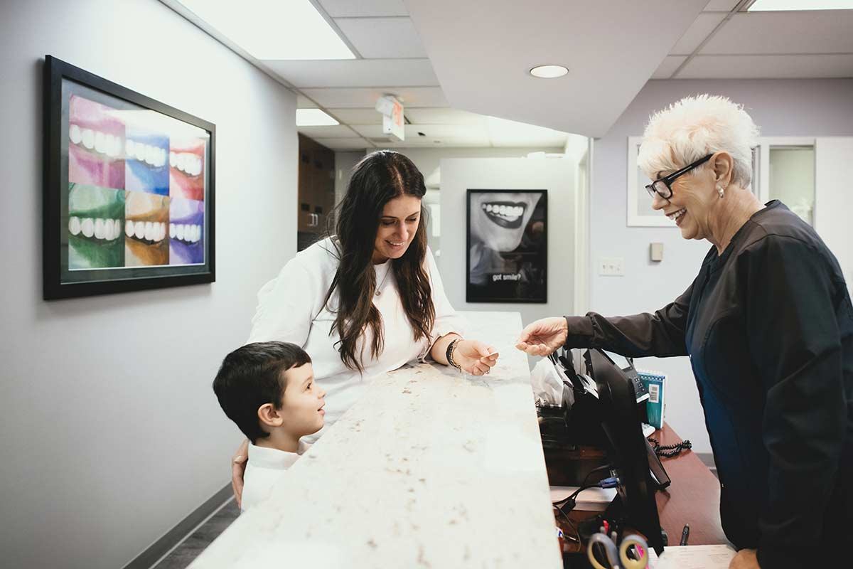 Photo of a patient and her son at the front desk with a team member