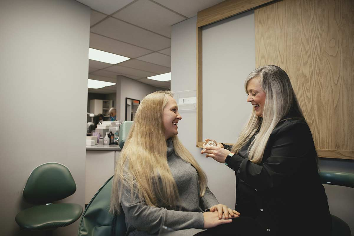 Photo of a hygienist showing a patient some models