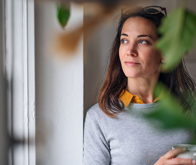 Woman looking out of a window with plant in foreground