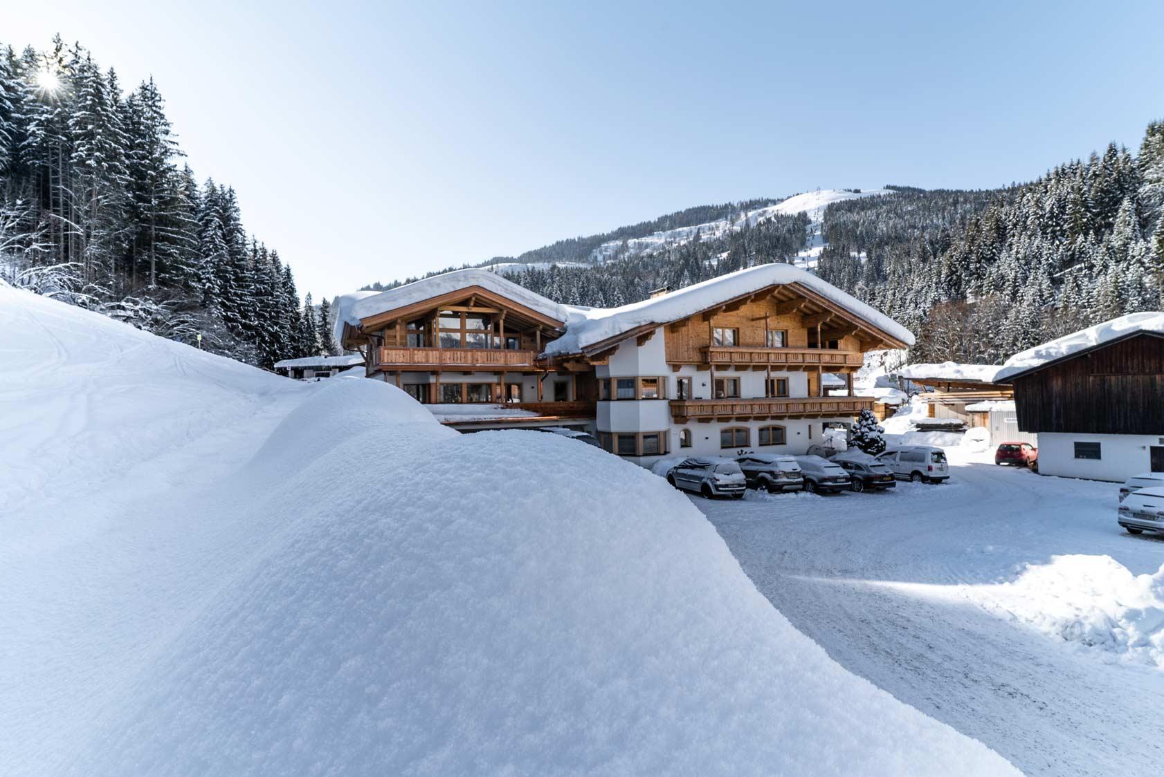 Auermühle Premium Penthouse Appartement – Aussenansicht mit Hartkaiser im Hintergrund im Winter
