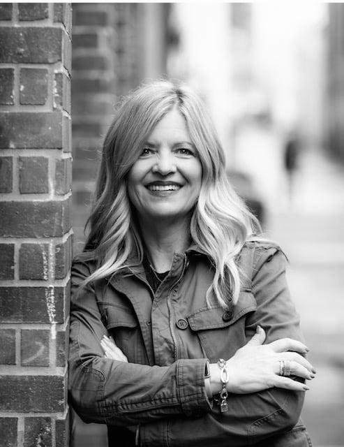 Black and white image of Lisa Pepper leaning against brick wall
