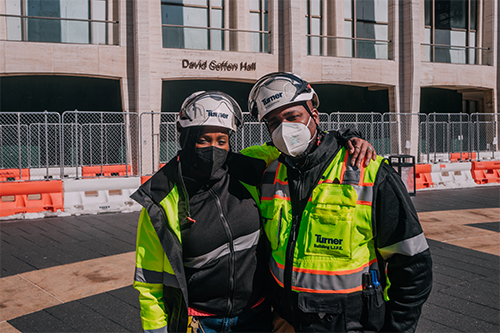 Image of two people of color contraction workers standing side my side