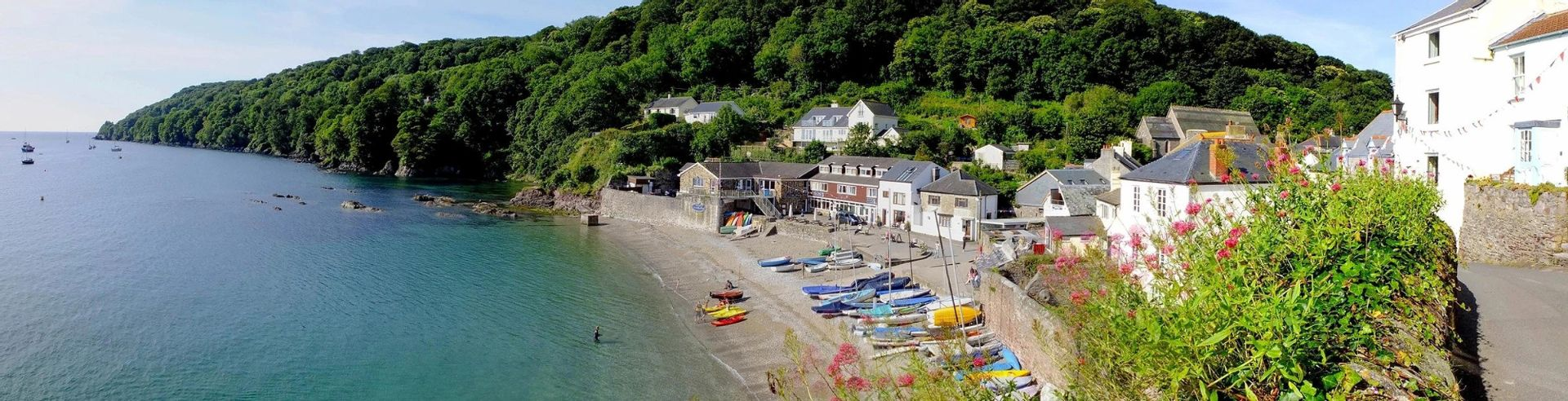 View over Cawsand Beach, lined with sailing boats